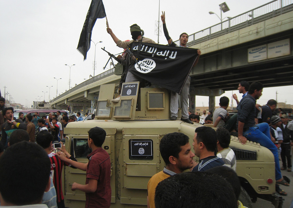 Description of . Al-Qaida fighters wave al-Qaida flags as they patrol in a commandeered Iraqi military vehicle in Fallujah, 40 miles (65 kilometers) west of Baghdad, Iraq, Sunday, March 30, 2014. Al-Qaida-linked fighters and their allies seized the city of Fallujah and parts of the Anbar provincial capital Ramadi in late December after authorities dismantled a protest camp. Like the camp in the northern Iraqi town of Hawija whose dismantlement in April sparked violent clashes and set off the current upsurge in killing, the Anbar camp was set up by Sunnis angry at what they consider second-class treatment by the Shiite-led government. (AP Photo)