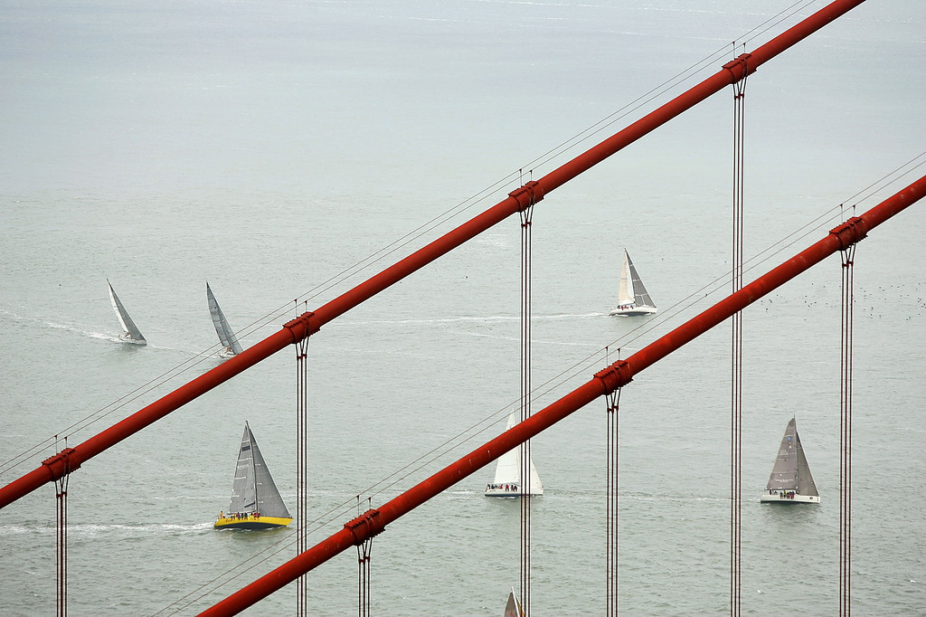 Description of . Boats sail past the Golden Gate Bridge during the Spinnaker Cup on May 22, 2009 in San Francisco, California. The Spinnaker Cup, which is one of six regattas in the San Francisco 2009 IRC Championship Series, is a distance race that starts in San Francisco and finishes in Monterey, California. (Photo by Ezra Shaw/Getty Images)