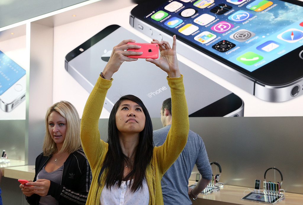 Description of . Wendy Sudsinsunthorn takes a picture with the new Apple iPhone 5C at an Apple Store on September 20, 2013 in Palo Alto, California.  (Photo by Justin Sullivan/Getty Images)