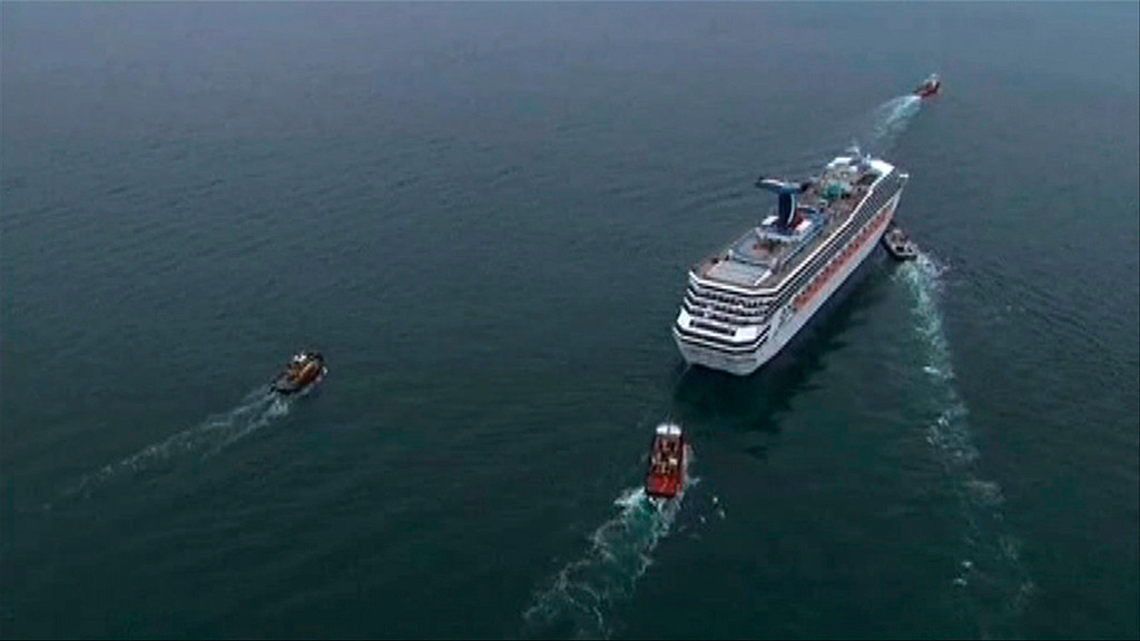 Description of . The cruise ship Carnival Triumph cruise ship is towed in this video frame grab from NBC News taken off the coast of Alabama, February 14, 2013. Three tugboats were hauling the disabled cruise ship Carnival Triumph cruise ship slowly into port in Mobile, Alabama, on Thursday where its arrival with more than 4,220 people aboard was expected later in the day, authorities said. REUTERS/NBC News/Handout