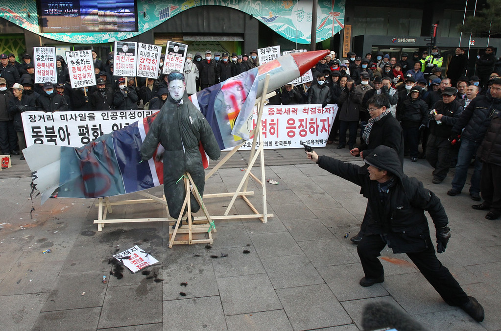 Description of . A South Korean protester aims a toy gun at an effigy of North Korean leader Kim Jong Un during a rally denouncing North Korea's rocket launch in Seoul, South Korea, Wednesday, Dec. 12, 2012.  North Korea successfully fired a long-range rocket on Wednesday, defying international warnings as the regime of Kim Jong Un took a giant step forward in its quest to develop the technology to deliver a nuclear warhead.  (AP Photo/Ahn Young-joon)