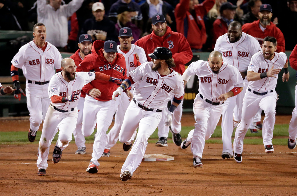 Description of . Boston Red Sox players run aftar Jarrod Saltalamacchia after Saltalamacchia hits the game winning single during Game 2 of the American League baseball championship series against the Detroit Tigers Sunday, Oct. 13, 2013, in Boston. The Red Sox won 6-5. (AP Photo/Charlie Riedel)