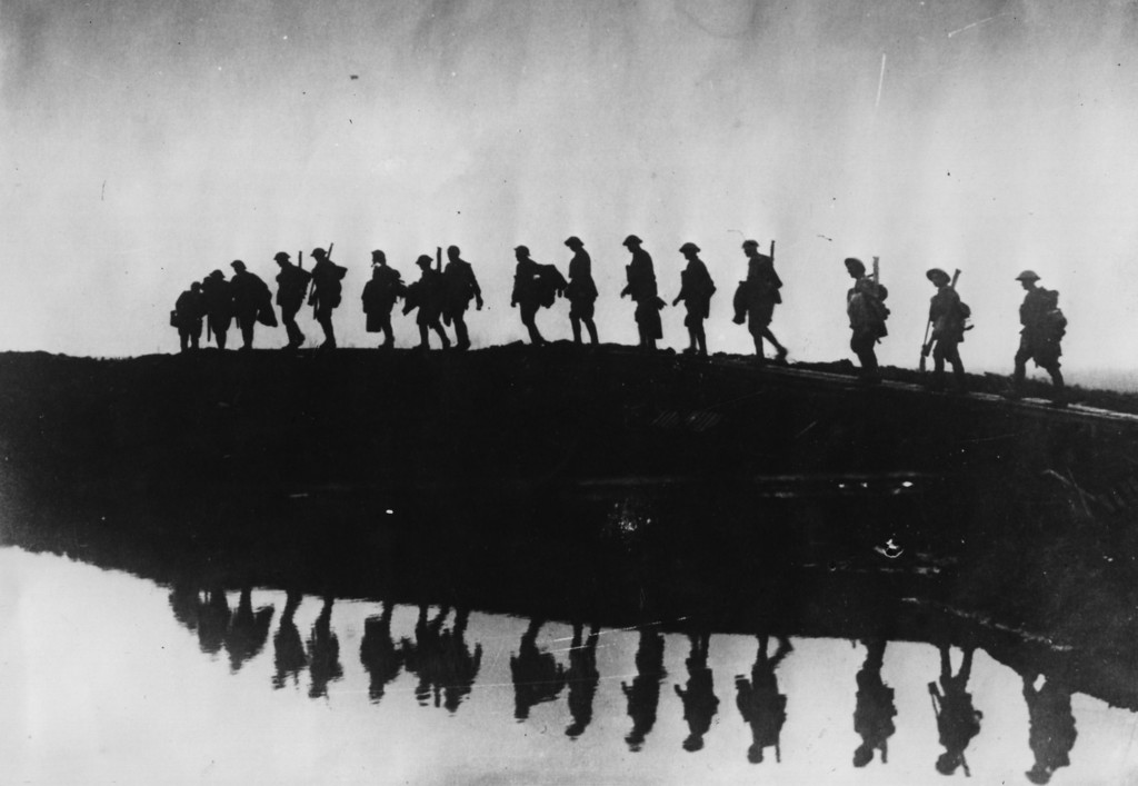 Description of . 5th October 1917: Supporting troops of the 1st Australian Division walking on a duckboard track near Hooge, in the Ypres Sector. They form a silhouette against the sky as they pass towards the front line to relieve their comrades, whose attack the day before won Broodseinde Ridge and deepened the Australian advance. (Photo by Frank Hurley/Hulton Archive/Getty Images)