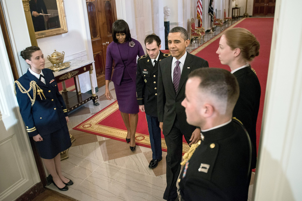 Description of . Former US Army Staff Sargent Clinton Romesha(C) walks with US President Barack Obama(R) and First Lady Michelle Obama (L) to the East Room for his Medal of Honor ceremony at the White House February 11, 2013 in Washington, DC. Sargent Romesha was awarded the Medal of Honor for his gallantry during an insurgent attack on Combat Outpost Keating in Afghanistan in 2009. AFP PHOTO/Brendan  SMIALOWSKI/AFP/Getty Images