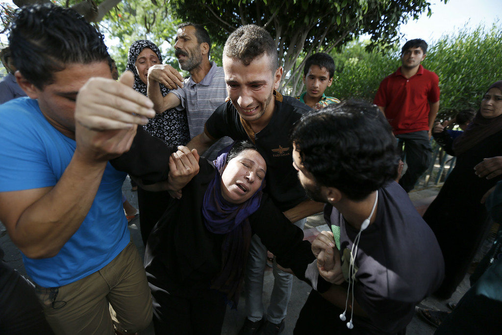 Description of . The mother of one of the four boys, all from the Bakr family, killed during Israeli shelling, collapses outside the al-Shifa hospital in Gaza City, on July 16, 2014. Four children were killed and several injured at a beach in Gaza City medics said, in Israeli shelling witnessed by AFP journalists. The strikes appeared to be the result of shelling by the Israeli navy against an area with small shacks used by fishermen. The deaths raised the overall toll in nine days of violence in Gaza to 213. AFP PHOTO / MOHAMMED ABED/AFP/Getty Images