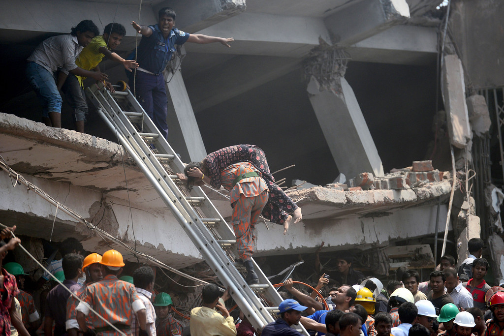 Description of . A Bangladeshi firefighter carries an injured garment worker after an eight-storey building collapsed in Savar, on the outskirts of Dhaka, on April 24, 2013. At least 82 people have died and 700 are injured after a eight-storey building housing several garment factories collapsed on the outskirts of Bangladesh's capital on Wednesday, a doctor said. AFP PHOTO/Munir uz ZAMAN/AFP/Getty Images