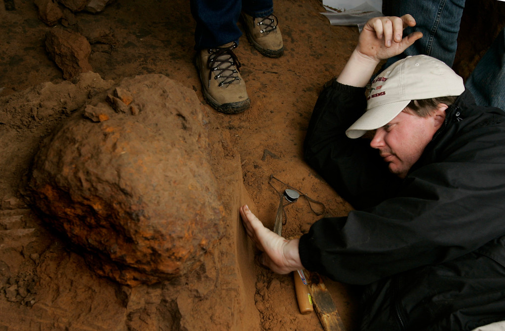 Description of . Houston Museum of Natural Science worker David Temple examines the soil beneath a meteor as workers from the museum dig up the find in a field near Greensburg, Kan., Monday, Oct. 16, 2006. (AP Photo/Charlie Riedel)