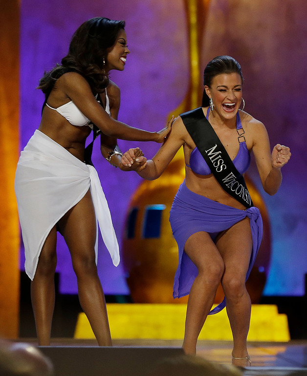 Description of . Miss Wisconsin Paula Mae Kuiper, right, reacts after finding out she's advancing beyond the lifestyle round as Miss Texas Ivana Hall congratulates her during the Miss America 2014 pageant, Sunday, Sept. 15, 2013, in Atlantic City, N.J. (AP Photo/Mel Evans)