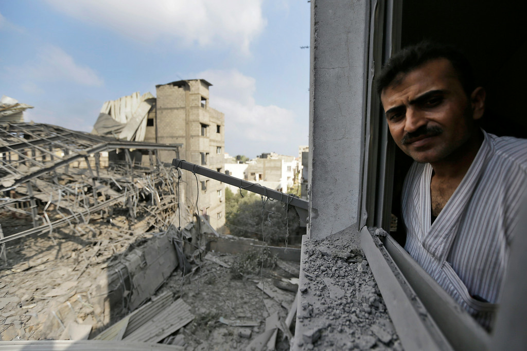 Description of . A Palestinian from a damaged neighboring apartment building inspects the damage of the offices of the Hamas movement's Al-Aqsa satellite TV station, left, in Gaza City, northern Gaza Strip, destroyed by an Israeli strike, Tuesday, July 29, 2014. (AP Photo/Lefteris Pitarakis)
