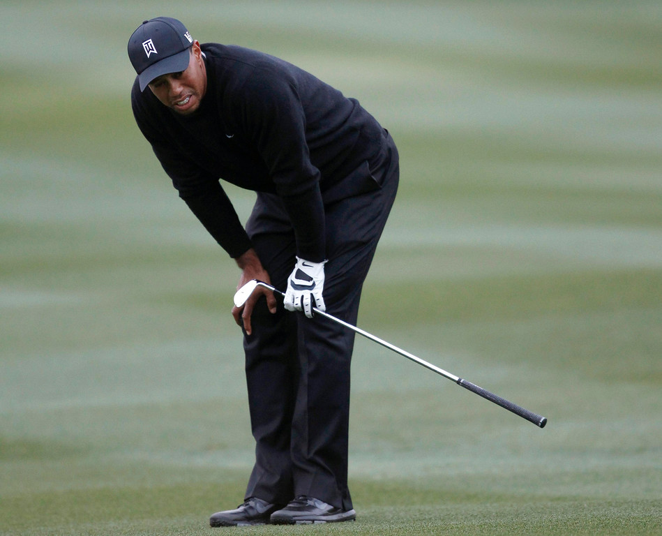 Description of . Tiger Woods of the U.S. reacts after hitting his second shot on the 15th hole against Charlies Howell III of the U.S. during the weather-delayed first round of the WGC-Accenture Match Play Championship golf tournament in Marana, Arizona February 21, 2013. REUTERS/Matt Sullivan