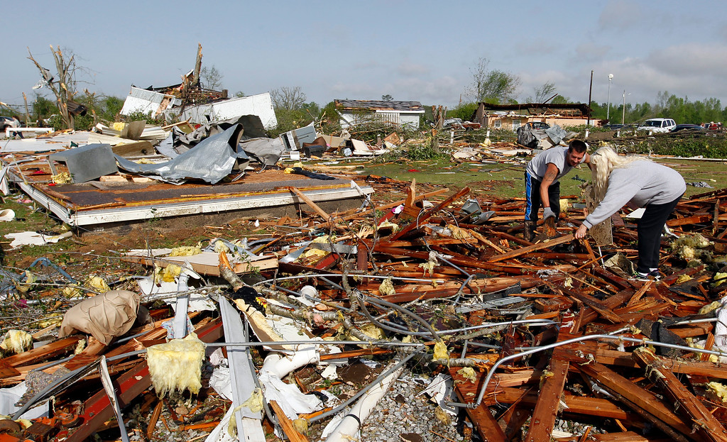 Description of . Kevin Toon, left, and Barb Smiley, right, begin cleaning up after a tornado passed through destroying the Billy Barbs mobile home park where they lived on Tuesday, April 29, 2014, in Athens, Ala.  (AP Photo/Butch Dill)