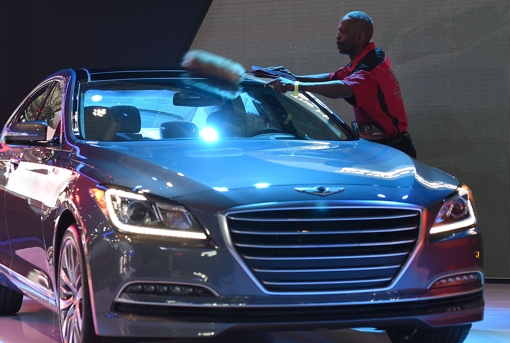 Description of . A worker cleans a 2015 Hyundai Genisis at the 2014 New Yrok Auto Show April 16, 2014 at the Jacob Javits Center in New York. The auto show opens to the public on April 18, and runs through the 27th. AFP PHOTO/Don  EMMERT/AFP/Getty Images