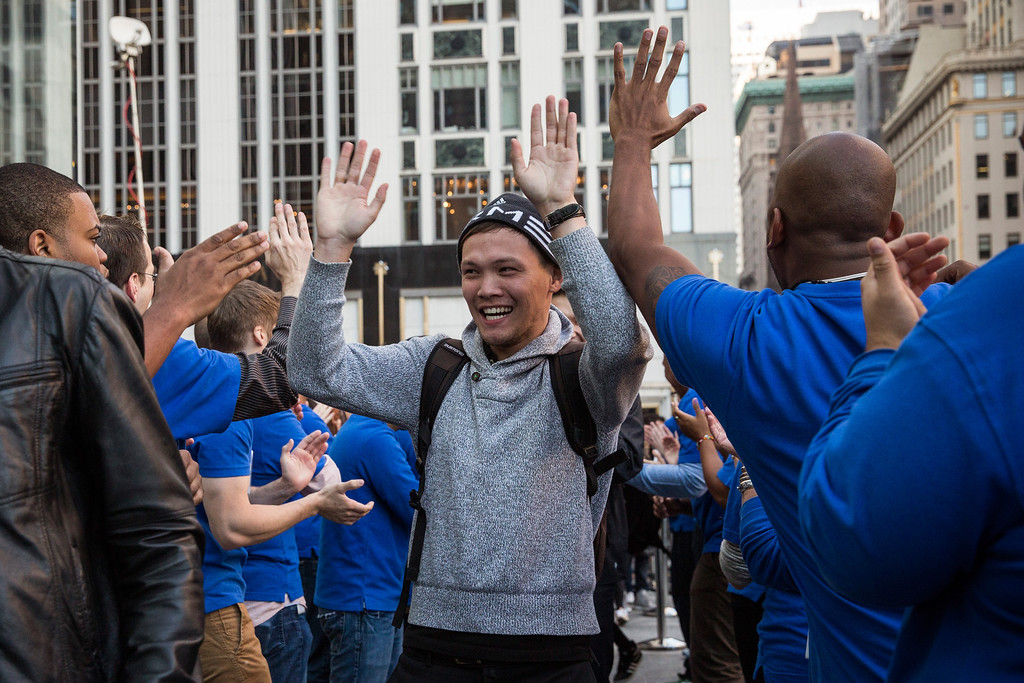 Description of . A customer is greeted by Apple employees while walking into the Fifth Avenue Apple store to buy an iPhone 5S on September 20, 2013 in New York City.  (Photo by Andrew Burton/Getty Images)