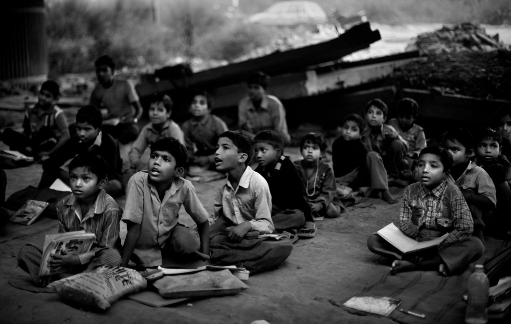 Description of . In this Nov. 6, 2012 photo, underprivileged Indian children attend a free school run under a metro bridge in New Delhi, India. This photo was one in a series of images by Associated Press photographer Altaf Qadri that received an honorable mention in the World Press Photo 2013 photo contest for the Contemporary Issues series category. (AP Photo/Altaf Qadri, File)