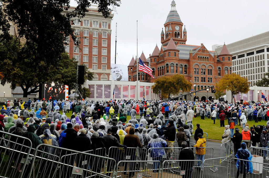 Description of . A crowd gathers before a ceremony to mark the 50th anniversary of the assassination of John F. Kennedy, Friday, Nov. 22, 2013, at Dealey Plaza in Dallas. President Kennedy's motorcade was passing through Dealey Plaza when shots rang out on Nov. 22, 1963. (AP Photo/Benny Snyder)