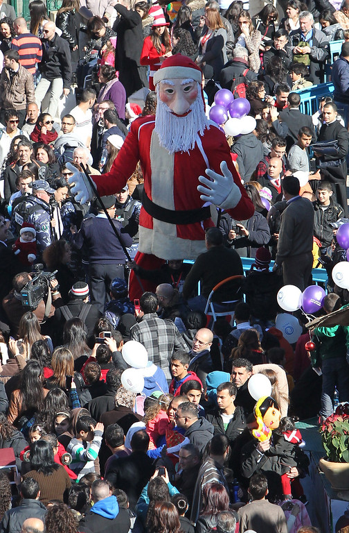 Description of . Christian pilgrims gather near a Santa Claus dummy at Manger Square, outside the Church of the Nativity, traditionally believed to be the birthplace of Jesus Christ, during Christmas celebrations in the West Bank biblical town of Bethlehem on December 24, 2013.  Palestinian president Mahmud Abbas urged Christian pilgrims from around the world to visit the Holy Land to mark the visit of Pope Francis, set for 2014, in a Christmas message.  HAZEM BADER/AFP/Getty Images