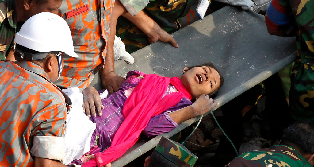Description of . A survivor lies on a stretcher after being pulled out from the rubble of a building that collapsed in Savar, near Dhaka, Bangladesh, Friday, May 10, 2013.  (AP Photo)