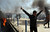An Egyptian flashes the victory sign after several protesters set fire to tires on the city's dock in an attempt to prevent ships from coming in to the strategic city of Port Said at the Mediterranean end of the Suez Canal, in Egypt, Saturday, March 9, 2013.(AP Photo/Ahmed Ramadan)