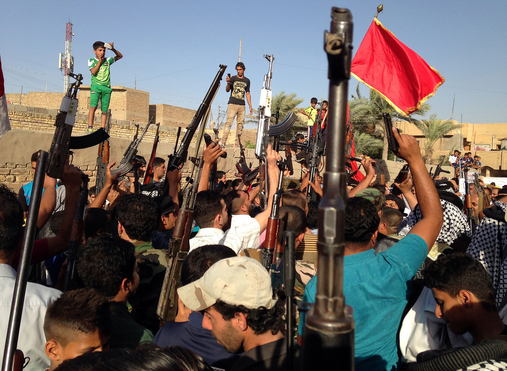 Description of . Shiite tribal fighters raise their weapons and chant slogans against the al-Qaida-inspired Islamic State of Iraq and the Levant (ISIL) in the east Baghdad neighborhood of Kamaliya, Iraq, Sunday, June 15, 2014. Emboldened by a call to arms by the top Shiite cleric, Iranian-backed militias have moved quickly to the center of Iraqís political landscape, spearheading what its Shiite majority sees as a fight for survival against Sunni militants who control of large swaths of territory north of Baghdad. (AP Photo)