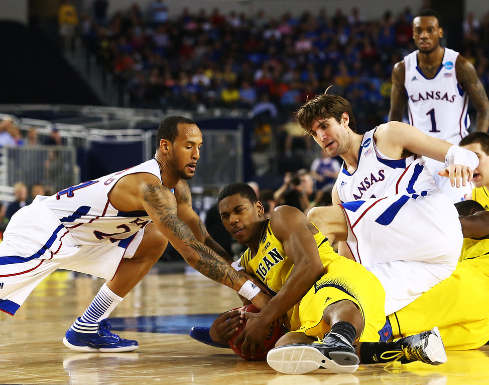 Description of . ARLINGTON, TX - MARCH 29:  Trey Burke #3 of the Michigan Wolverines vies for a loose ball with Jeff Withey #5 and Travis Releford #24 of the Kansas Jayhawks in the second half during the South Regional Semifinal round of the 2013 NCAA Men\'s Basketball Tournament at Dallas Cowboys Stadium on March 29, 2013 in Arlington, Texas.  (Photo by Ronald Martinez/Getty Images)
