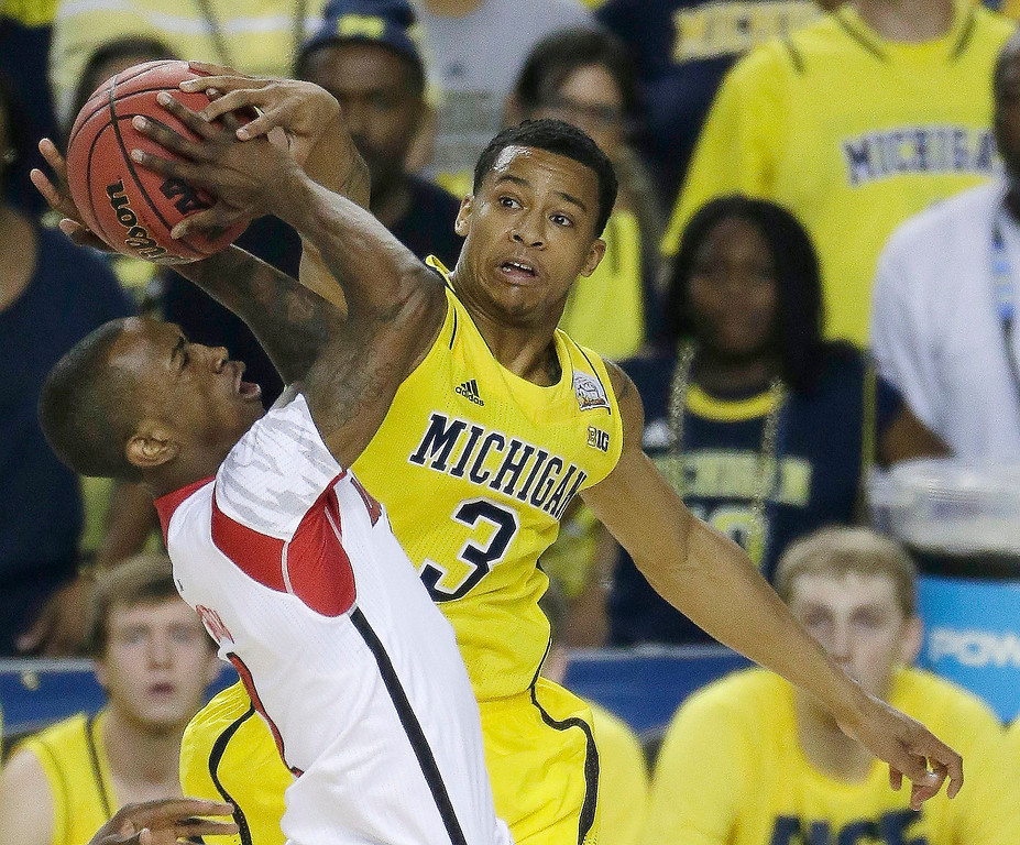 Description of . Michigan guard Trey Burke (3) works against Louisville guard Russ Smith (2) during the first half of the NCAA Final Four tournament college basketball championship game Monday, April 8, 2013, in Atlanta. (AP Photo/Chris O'Meara)