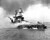 In this image provided by the U.S. Navy, crewmen of the USS Nevada still fight flames on the battleship, battered in the Japanese aerial attack on Pearl Harbor on Dec. 7, 1941, after the big ship is beached at Hospital Point. (AP Photo/U.S. Navy)