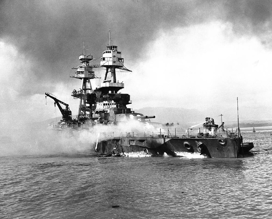 Description of . In this image provided by the U.S. Navy, crewmen of the USS Nevada still fight flames on the battleship, battered in the Japanese aerial attack on Pearl Harbor on Dec. 7, 1941, after the big ship is beached at Hospital Point. (AP Photo/U.S. Navy)