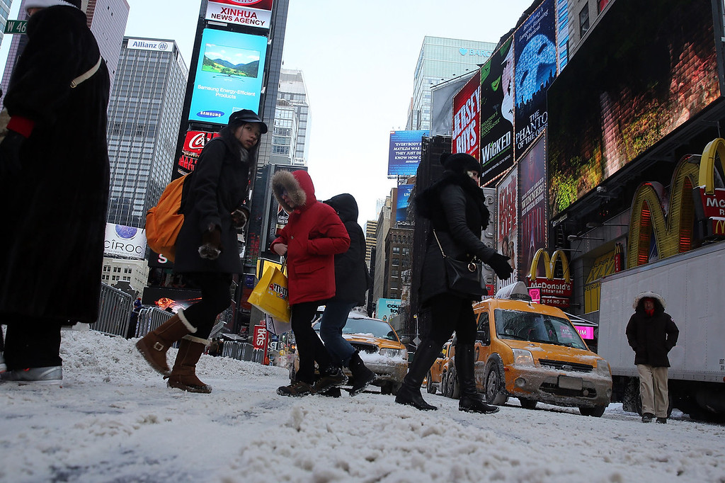 Description of . People walk through a cold and snow covered Times Square following a snow storm that left up to 8 inches of snow on January 3, 2014 in New York, United States. The major winter snowstorm, which forced New York City public schools to close and shut down the Long Island Expressway, is being viewed as a test for the new mayor of New York City Bill de Blasio. Dangerously cold temperates are predicted for the day and evening hours.  (Photo by Spencer Platt/Getty Images)