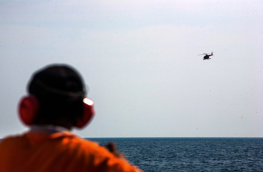 Description of . A member of Indonesia's National Search and Rescue looks on as a helicopter flies over the waters during search operations in the Andaman sea area around northern tip of Indonesia's Sumatra island for the missing Malaysian Airlines flight MH370 on March 21, 2014. The search for MH370 has been compared to that of an Air France jet that crashed into the Atlantic Ocean in 2009 with the loss of 228 lives. AFP PHOTO / CHAIDEER  MAHYUDDIN/AFP/Getty Images