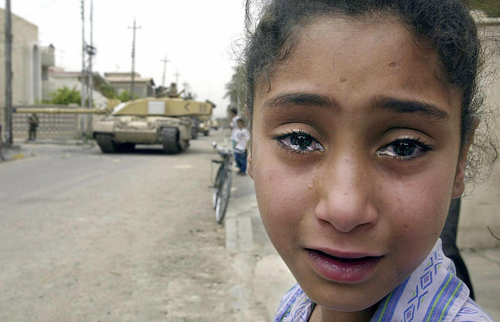 Description of . A young Iraqi girl cries as a British Challenger tank moves in on the Baath party office in Basra April 8, 2003. (Odd Andersen/AFP/Getty Images)