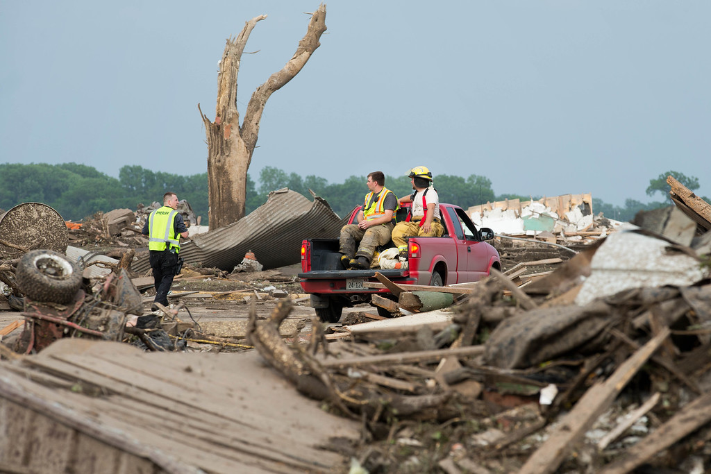 . Firefighters and police survey the damage in Pilger, Neb.,  on Monday, June 16, 2014.  The National Weather Service says the storm that struck northeast Nebraska appears to have produced four tornadoes, one of which ravaged the town of Pilger.   (AP Photo/The World-Herald, Ryan Soderlin)