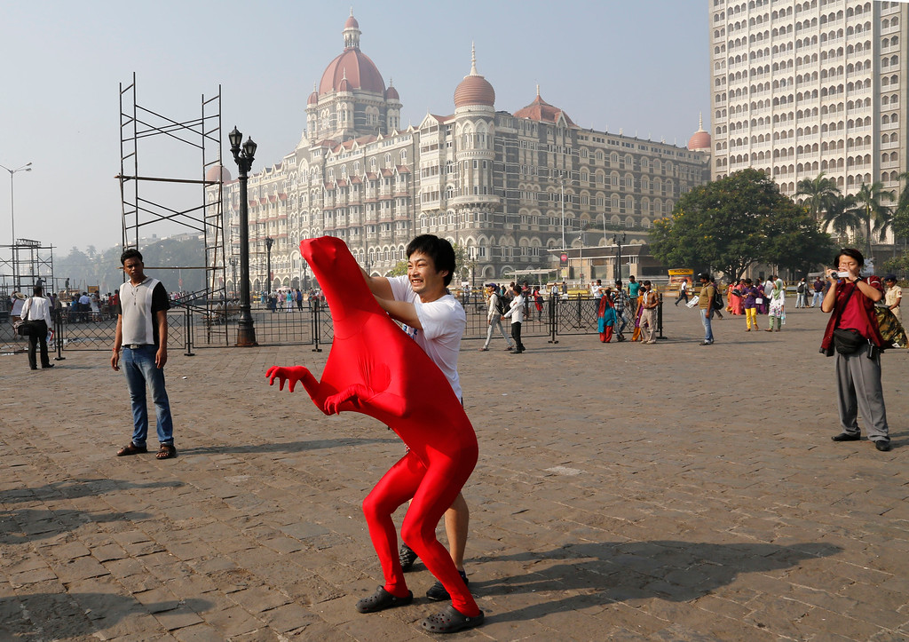 Description of . Members of the 3Gaga Heads, a 3-member comedy group from Japan, rehearse at the promenade outside the Taj Mahal Hotel, one of the sites of the Mumbai terror attack, during the 5th anniversary of the attack in Mumbai, India, Saturday, Nov. 26, 2013. The attack by Pakistani gunmen in India\'s financial capital on Nov. 26, 2008 killed 166 people and shattered relations between the nuclear-armed neighbors.  (AP Photo/Rajanish Kakade)
