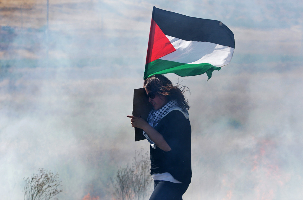 Description of . A Palestinian woman holds a national flag as she makes her way through tear gas during a demonstration against the Israeli military action in Gaza, near the West Bank town of Nablus, Wednesday, July 16, 2014.  Hundreds of Palestinian families, their children crying, fled Wednesday, as Israel intensified airstrikes on Hamas targets, including homes of the movement's leaders, following failed Egyptian cease-fire efforts. Before the renewed bombardment, Israel had told tens of thousands of residents of border areas to evacuate their neighborhoods. (AP Photo/Nasser Ishtayeh)