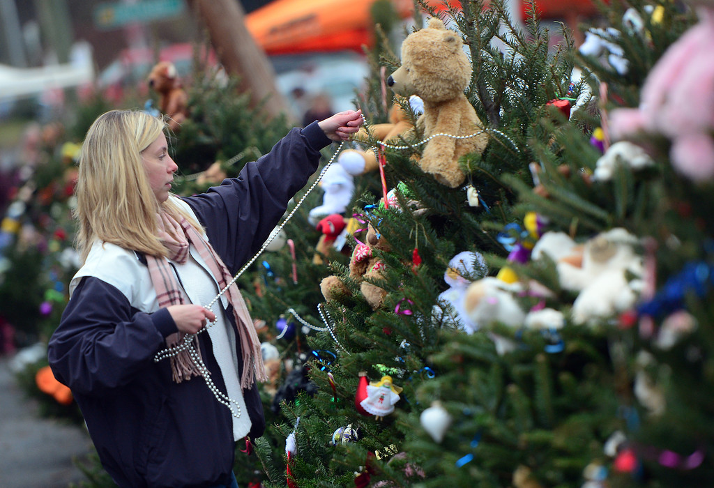 Description of . A teenager decorates Christmas trees set up at a makeshift shrine to the victims of a elementary school shooting in Newtown, Connecticut, December 16, 2012.  A young gunman slaughtered 20 small children and six teachers on December 14,2012 after walking into a school in an idyllic Connecticut town wielding at least two sophisticated firearms.  EMMANUEL DUNAND/AFP/Getty Images