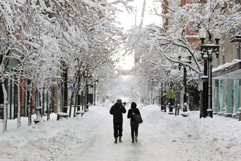 . A couple walks down Westminster Street in downtown Providence, R.I., after a winter storm dumped two feet of snow on the area, Saturday, Feb. 9, 2013. (AP Photo/Stew Milne)