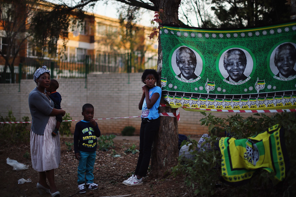 Description of . PRETORIA, SOUTH AFRICA - JUNE 29:  A girl stands besides an ANC flag depicting Nelson Mandela outside the MediClinic Heart hospital where former South African President Nelson Mandela is being treated on June 29, 2013 in Pretoria. US President Barack Obama met with the former South African leader's family to offer prayers as Mandela continues to be treated for a lung infection.  (Photo by Dan Kitwood/Getty Images)