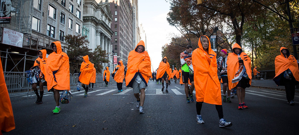 Description of . Runners finished with the ING New York City Marathon walk through the streets cloaked in blankets on November 3, 2013 in New York City. With the Boston Marathon bombing from earlier this year still fresh in many minds, security is especially high this year at the New York City marathon.  (Photo by Andrew Burton/Getty Images)