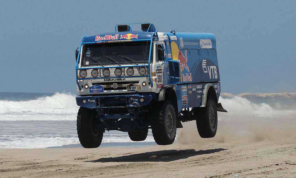 Description of . Eduard Nikolaev, Sergey Savostin and Vladimir Rybakov of Russia race their Kamaz truck on a beach in the 4nd stage of the 2013 Dakar Rally from Nazca to Arequipa, Peru, Tuesday, Jan. 8, 2013. The race finishes in Santiago, Chile, on Jan. 20. (AP Photo/Victor R. Caivano)