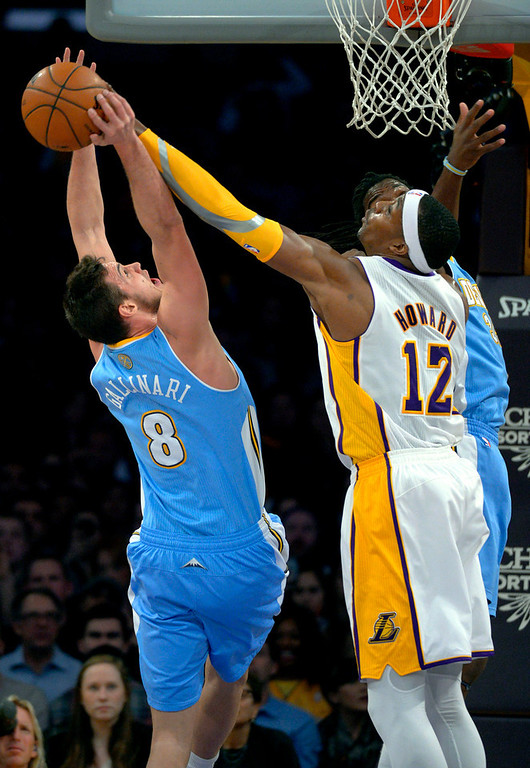 Description of . Los Angeles Lakers center Dwight Howard, right, blocks a shot by Denver Nuggets forward Danilo Gallinari, of Italy, during the first half of their NBA basketball game, Sunday, Jan. 6, 2013, in Los Angeles. (AP Photo/Mark J. Terrill)
