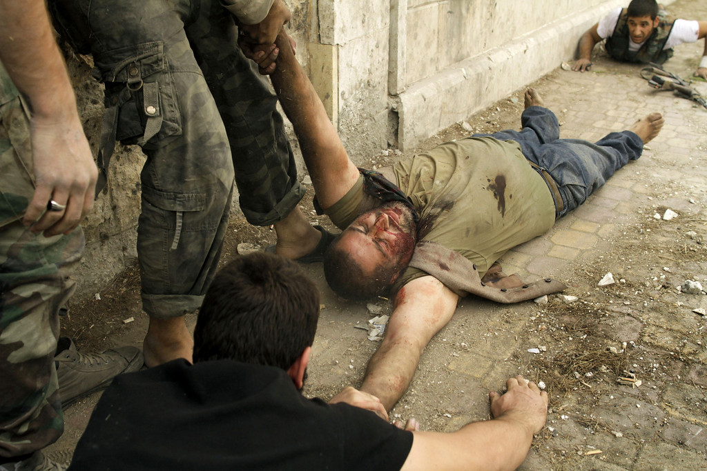 Description of . Members of the Al-Baraa bin Malek batallion, part of the Free Syria Army's Al-Fatah brigade, duck to the ground as they pull a man who was shot by a sniper twice in the Bustan al-Basha district of the northern city of Aleppo on October 20, 2012. Due to the risk of being shot by the sniper, no one was able to rescue the man who eventually ran towards rebels, only to be shot by the sniper a second time. Rebels then pulled him and rushed him to a hospital, though it is not known if he survived. Three civilians were shot on this main road in the space of three hours by the same sniper. Javier Manzano/AFP/Getty Images