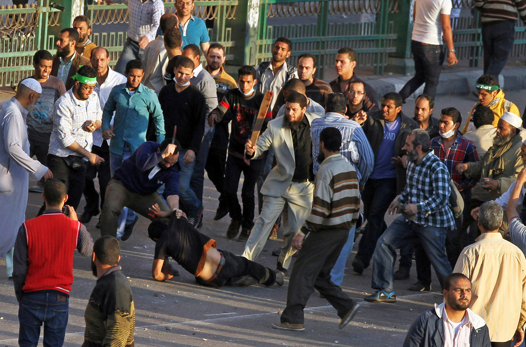 Description of . Muslim Brotherhood supporters beat a protester in Tahrir Square, as supporters and opponents of Egypt's Islamist president battle in Cairo, Egypt, Friday, April 19, 2013. (AP Photo/Ahmed Gomaa, File)