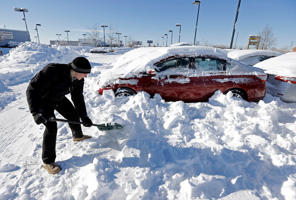 . A salesmen at a car dealer digs out cars covered in snow at a dealership in Indianapolis Tuesday, Jan. 7, 2014, as temperatures hovered around zero.  The subzero cold followed inches of snow and high winds that made traveling treacherous. (AP Photo/Michael Conroy)