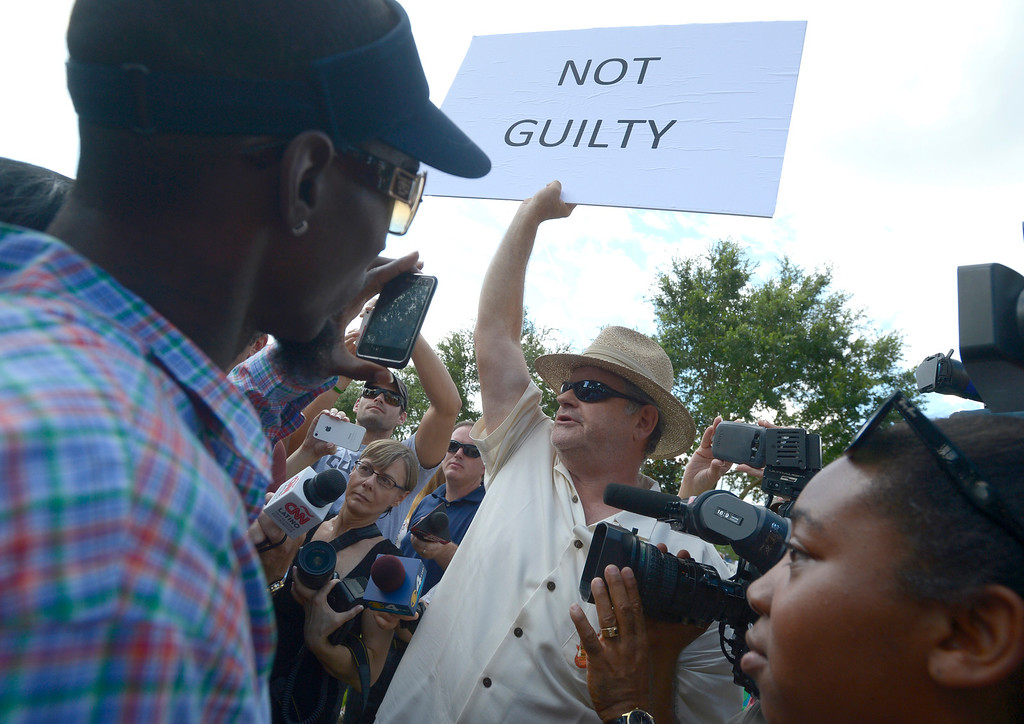 Description of . A man who would not provide his name, shows his support for George Zimmerman outside the Seminole County Courthouse in Sanford, Fla., Saturday, July 13, 2013.  Zimmerman has been charged in the 2012 shooting death of Trayvon Martin.(AP Photo/Phelan M. Ebenhack)