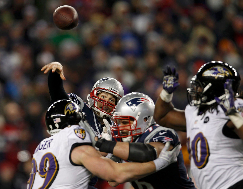 Description of . New England Patriots quarterback Tom Brady (12) passes under pressure from the Baltimore Ravens in the NFL AFC Championship football game in Foxborough, Massachusetts, January 20, 2013. REUTERS/Adam Hunger