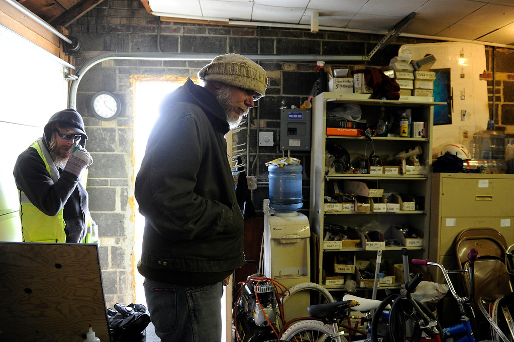 Description of . AURORA, CO - NOVEMBER 21: Howard Jarrett, center, surveys the Second Chance Bicycle Shop on November 21, 2013, in Aurora, Colorado. Housed in the Aurora Warms the Night garage, the shop provides homeless clients with an outlet to learn a skill and apply it to help others. A client must work in the shop for six weeks before he or she can take a fixed-up bicycle away with them. Jarrett has been working in the shop for several years, and says it helped him along his path to recovery. (Photo by Anya Semenoff/YourHub)