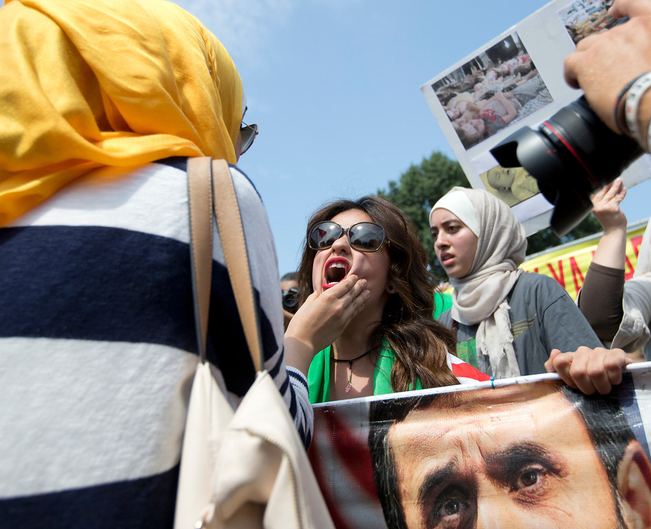 Description of . An unidentified Syrian protester, left, who opposes U.S. military action in Syria, grabs the face of Asmaa Al-Ghafari, a self-described