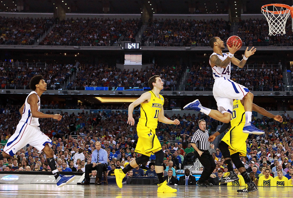 Description of . ARLINGTON, TX - MARCH 29:  Travis Releford #24 of the Kansas Jayhawks goes up against the Michigan Wolverines in the first half during the South Regional Semifinal round of the 2013 NCAA Men\'s Basketball Tournament at Dallas Cowboys Stadium on March 29, 2013 in Arlington, Texas.  (Photo by Ronald Martinez/Getty Images)