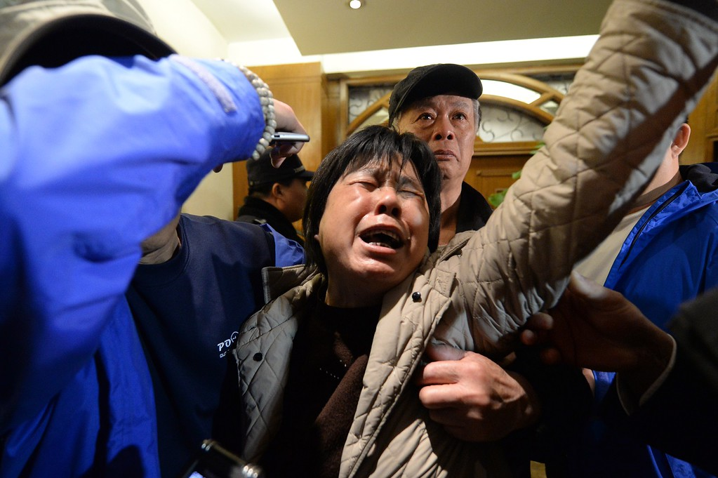 Description of . A relative (C) of passengers on Malaysia Airlines flight MH370 cries after hearing the news that the plane plunged into Indian Ocean at a hotel in Beijing on March 24, 2014.  The missing Malaysia Airlines jet came down in the Indian Ocean, Prime Minister Najib Razak said March 24, as the airline reportedly told relatives it had been lost and that none on board survived. AFP PHOTO / GOH  CHAI HIN/AFP/Getty Images