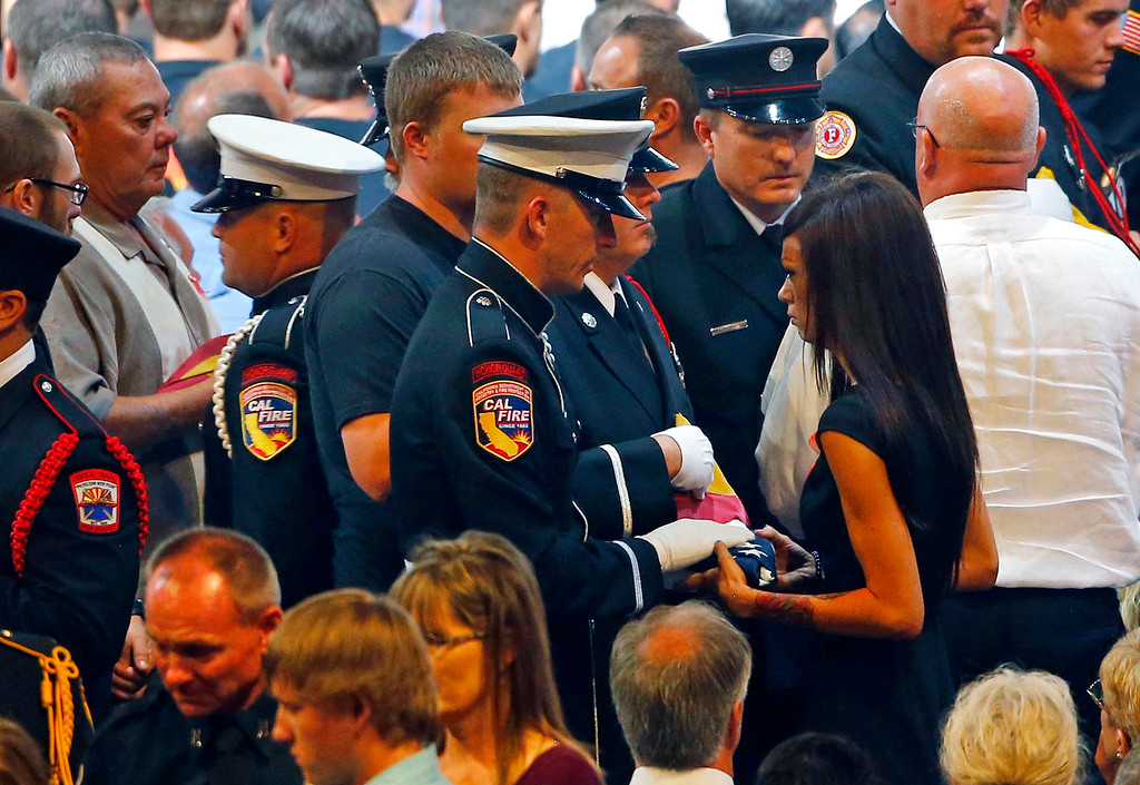 Description of . An honor guard presents Juliann Ashcraft, wife of fallen firefighter Andrew Ashcraft, with an American flag during a memorial service at Tim's Toyota Center in Prescott Valley, Ariz.,  Tuesday, July 9, 2013, for the 19 Granite Mountain hotshot firefighters that were killed on June 30 while battling the Yarnell Hill Fire. (AP Photo/The Arizona Republic, David Kadlubowski, Pool)