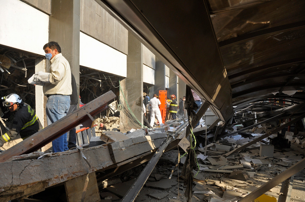 Description of . Firefighters belonging to the Tacubaya sector and workers dig for survivors after an explosion at a building adjacent to the executive tower of Mexico's state-owned oil company PEMEX, in Mexico City, Thursday Jan. 31, 2013.    (AP Photo/Guillermo Gutierrez)